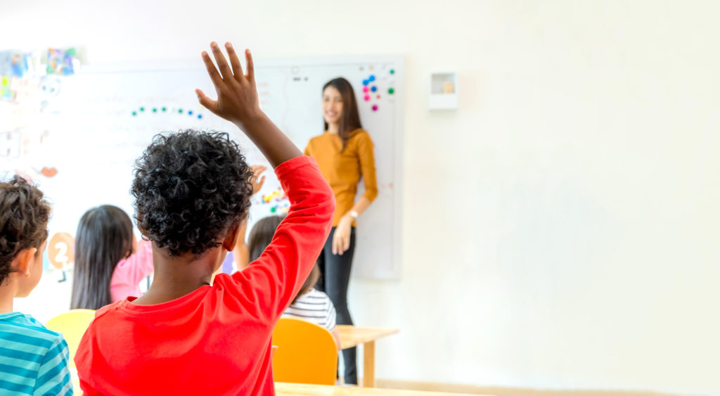 African American ethnicity kid hand up for answer question of teacher in classroom,Kindergarten preschool education concept,Mock up banner space for adding your text.